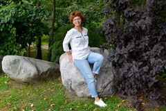 The cheerful woman of average years sits on a boulder in the par Royalty Free Stock Photography