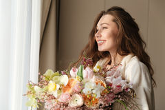 Cheerful woman in bathrobe with boquet of flowers at home. Cheerful pretty young woman in bathrobe with boquet of flowers standing near the window at home royalty free stock images