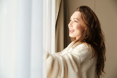 Cheerful woman in bathrobe smiling and looking at the window. Cheerful pretty young woman in bathrobe smiling and looking at the window at home Royalty Free Stock Photo