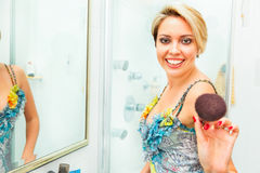 Cheerful woman in bathroom extends brush in camera Royalty Free Stock Photo