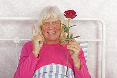 Cheerful woman in bed with rose Stock Images