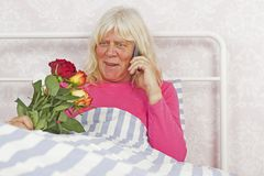 Cheerful woman in bed with roses and telephone Royalty Free Stock Photos