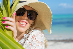 Cheerful woman behind palm leaf on the beach Stock Image