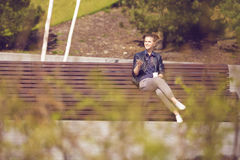 Cheerful woman on a bench with mobile phone royalty free stock photo