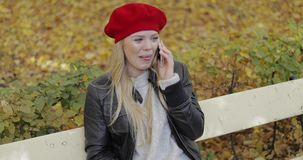 Cheerful woman in beret speaking on phone stock video