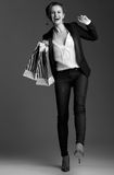 Cheerful woman with big shopping bags against grey background Stock Images