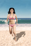 Cheerful woman in bikini jogging on beach Stock Photography