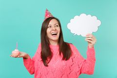 Cheerful woman in birthday hat looking up, hold cake with candle, empty blank Say cloud speech bubble for promotional. Content isolated on blue background royalty free stock photography