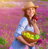 Cheerful woman biting apple. Closeup on nice cheerful woman wearing straw hat biting apple, sunset light, pink floral glade, countryside, autumnal harvest season royalty free stock image