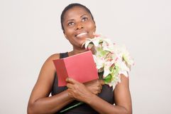 Happy woman holding flowers and a card Stock Photo