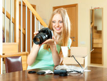 Cheerful woman with blond hair unpacking for new digital camera Stock Image