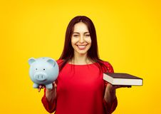 Cheerful woman with book and moneybox. Content female student showing book and piggy bank content with savings and scholarship isolated on yellow background stock photography
