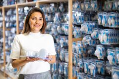 Cheerful woman buyers energy saving lamp at hardware store