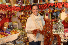 Cheerful woman buying Christmas tinsel garland Royalty Free Stock Photo