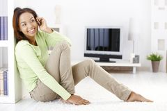 Cheerful woman calling in living room stock images