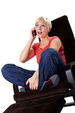 Cheerful woman calls on phone in an armchair Stock Image