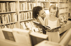 Cheerful woman with child reading open book. Young cheerful women with child in school age reading open book in bookstore stock image