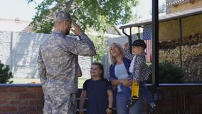 Excited family meeting serviceman at home. Cheerful woman with children welcoming father and husband from military service looking super excited stock video footage