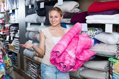 Cheerful woman choosing blanket. In bedding section in shop Stock Photos