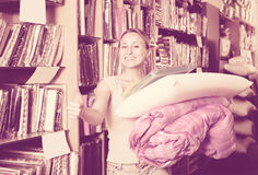Cheerful woman choosing blanket and pillow. Portrait of cheerful woman choosing blanket, pillow and textile in bedding section in shop Royalty Free Stock Image