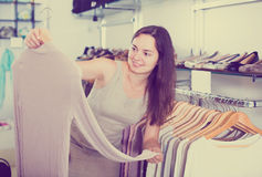 Cheerful woman choosing new blouse in apparel shop Stock Photography
