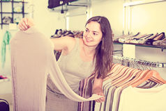 Cheerful woman choosing new blouse in apparel shop. Cheerful woman choosing new long sleeve blouse in apparel shop royalty free stock image