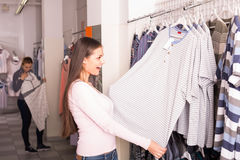 Cheerful woman choosing pajamas top for man in shop Stock Images