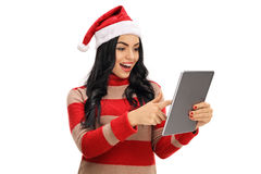 Cheerful woman with a christmas hat looking at a tablet Royalty Free Stock Image