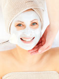 Cheerful woman with a clay mask on her face Stock Image