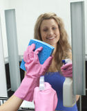 Cheerful woman cleaning bathroom's mirror. At home stock images