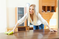 Cheerful  woman cleaning table at home Royalty Free Stock Images