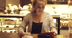 Cheerful woman with coffee and tablet stock video