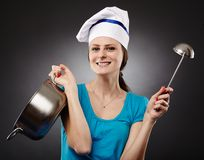 Cheerful woman cook holding a pot and a soup ladle Stock Photo