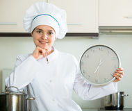 Cheerful woman in cook uniform with big clock Royalty Free Stock Photo