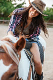 Cheerful woman cowgirl enjoying riding horse in village. Cheerful pretty young woman cowgirl enjoying riding horse in village Stock Photography
