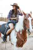 Cheerful woman cowgirl sitting and riding horse in village. Cheerful pretty young woman cowgirl sitting and riding horse in village Royalty Free Stock Photo