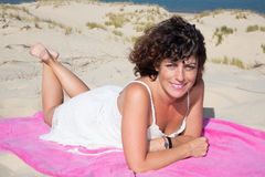 Cheerful woman curly hair in white dress lying on the white sand beach royalty free stock photos