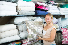 Cheerful woman customer buying fluffy pillow Stock Image