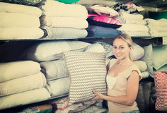 Cheerful woman customer buying fluffy pillow Royalty Free Stock Image
