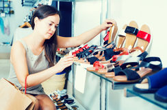 Cheerful woman customer selecting shoes in footgear center. Portrait of cheerful woman customer selecting shoes in footgear center Stock Image