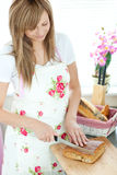 Cheerful woman cutting bread in the kitchen. At home Stock Photos