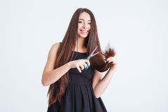 Cheerful woman cutting splitting ends of long hair with scissors Stock Photos