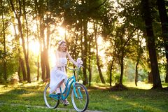 Cheerful woman cycling in the park. Horizontal shot of a young woman wearing elegant white dress cycling in the park on summer evening copyspace nature sunset Stock Images