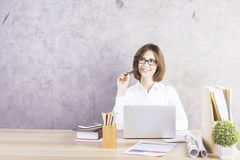 Cheerful woman daydreaming in office. Cheerful businesswoman daydreaming in modern office interior. Textured concrete wall in the background Stock Image