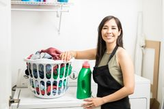 Cheerful woman with dirty clothes in white basket kept over wash. Young woman with detergent and laundry standing wearing black apron standing by washing machine Stock Image