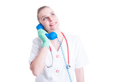 Cheerful woman doctor talking to a classic blue phone Royalty Free Stock Photography