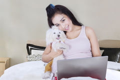 Cheerful woman and dog plays with a laptop Royalty Free Stock Photo