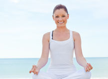 Cheerful woman doing yoga by the sea Stock Photo