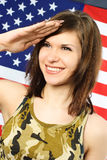 Cheerful woman dressed in camouflage salutes Stock Photos