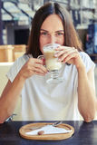 Cheerful woman drinking cappuccino Royalty Free Stock Photos